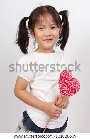 Young girl holding lollipop - stock photo