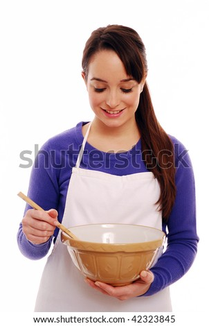 Young girl holding mixing bowl and wooden spoon - stock photo