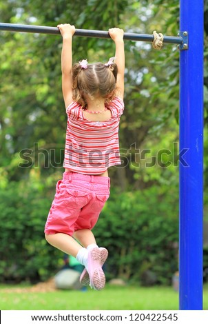 Young girl holding on the bar - stock photo