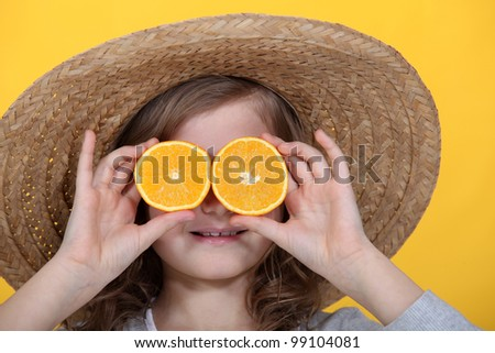 Young girl holding orange slices in front of her eyes - stock photo