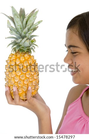 Young girl holding pineapple and smiling - stock photo