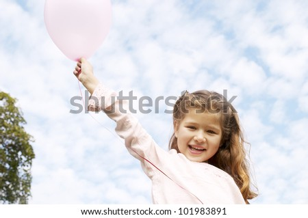 Young girl holding pink balloons against a blue sky and smiling in the park. - stock photo