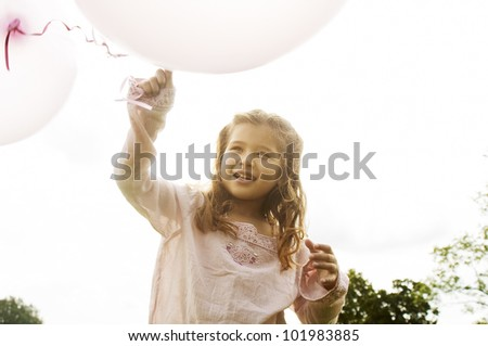 Young girl holding pink balloons in the air and smiling in the park. - stock photo
