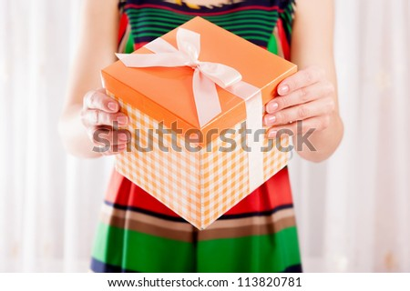 Young girl holding present box with ribbon bow - stock photo