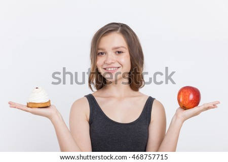 Young girl holding red apple and cupcake in her hands, smiling and deciding which to choose. Concept of healthy food. Portrait. Isolated