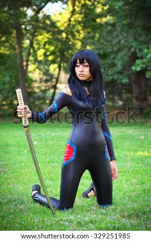 Young girl holding samurai sword. Original cosplay character - stock photo