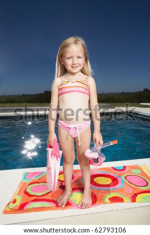 Young girl holding scuba gear - stock photo