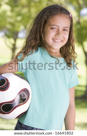 Young girl holding soccer ball outdoors smiling - stock photo