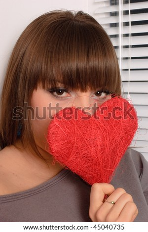 young girl holding the heart in the hands - stock photo