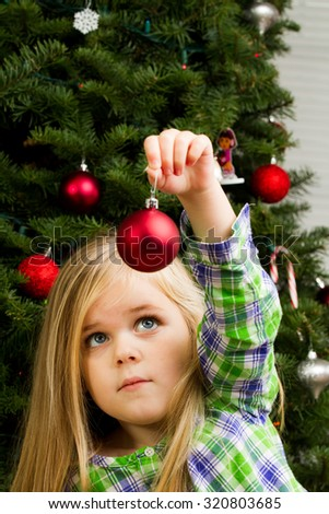 young girl holding up a christmas tree decoration - stock photo