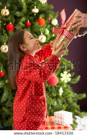 Young Girl Holding Wrapped Present In Front Of Christmas Tree - stock photo