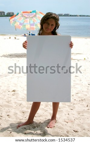 young girl holds blank sign on beach