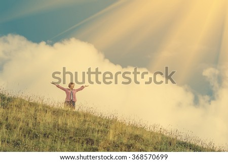 Young girl holds hands up against the sky and hillside
