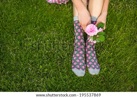 Young girl holds rose flower while sitting on grass. daylight, focus on flower - stock photo