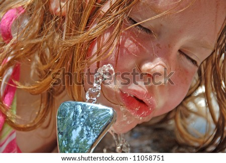 Young girl hot and thirsty after exercise, getting drink of water from fountain - stock photo