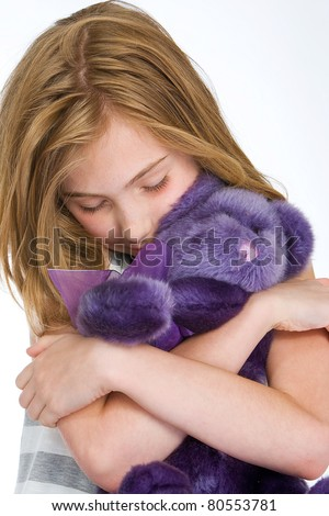 young girl hugging a purple teddy bear - stock photo
