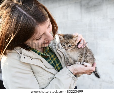 Young girl hugging a small kitten - stock photo