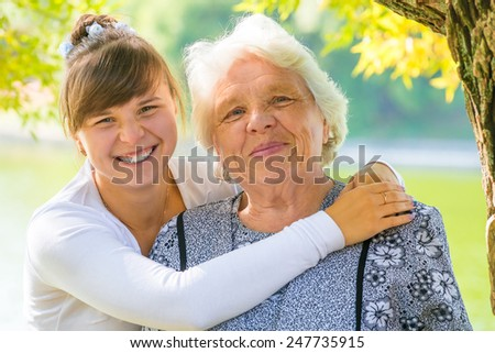 young girl hugging her beloved grandmother - stock photo