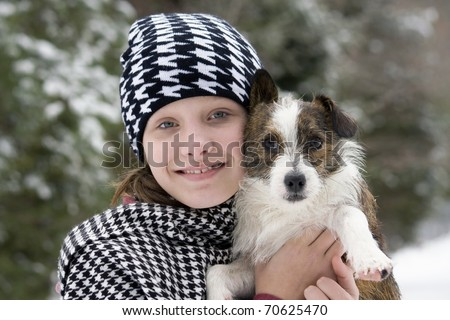 Young girl hugging her cute puppy outside in the snow - stock photo