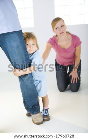 Young girl hugging man's leg. Behind girl's mother kneeling and holding a girl. A girl looking at camera. Focused on Young girl. - stock photo