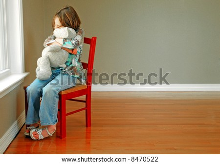 Young girl hugging stuffed animal looking out of window - stock photo