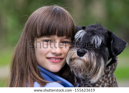 Young girl hugs her adorable dog - stock photo