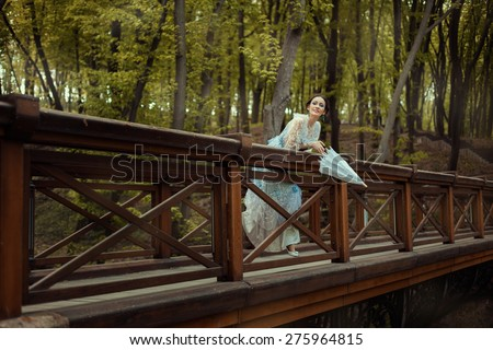 Young girl hung down from the bridge and vintage looks. In her hands she holds an old-fashioned umbrella. Around the fairy forest. - stock photo