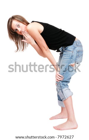 Young girl i ragged jeans bending forward with shocked facial expression