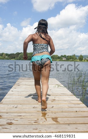 Young girl in a bathing suit runs along a wooden pier to jump into a lake.  Mont Laurier, Quebec, Canada near Montreal.