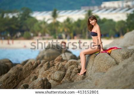 Young girl in a bikini sitting on the rock at Karon beach, Phuket island, Thailand - stock photo