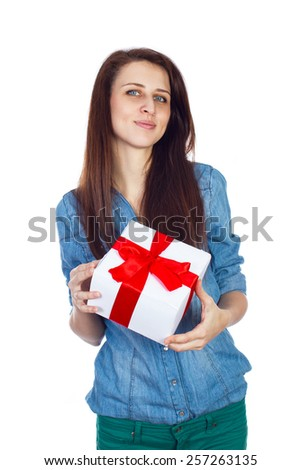 Young girl in a blue denim shirt and green jeans with gift box in hands. Beautiful brunette with long hair isolated on white background. White gift box with red ribbon - stock photo