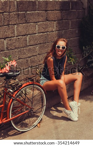 young girl in a blue t-shirt and denim shorts in sunglasses posing with red bicycle with a basket of classic vintage retro style bali indonesia hipster white sneakers - stock photo