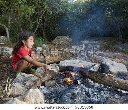 young girl in a campfire min a mediterranean forest