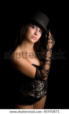 Young girl in a corset coquets holds a hand in a lacy glove on a the  cylinder hat