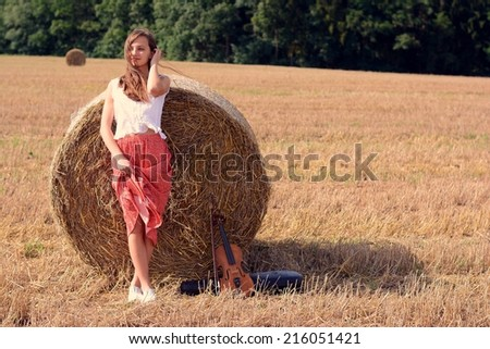 Young girl in a field in the village with violin - stock photo