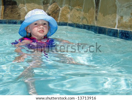 Young girl in a floppy hat in a suburban pool - stock photo