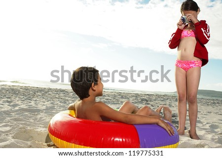 Young girl in a pink bikini photographing her brother who is lying in a colourful inflated plastic ring on the beach sand