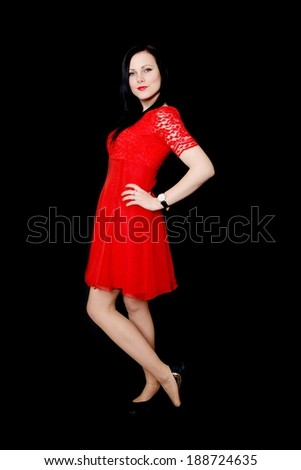 Young girl in a red dress on a black background