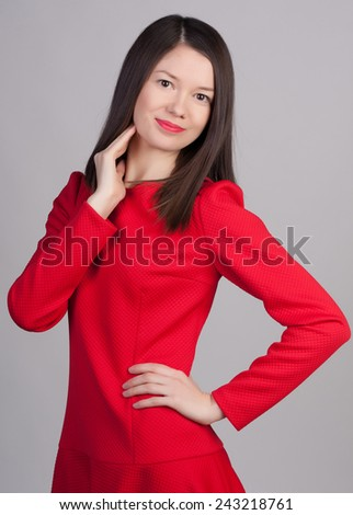 Young girl in a red dress on a grey background. Fashion photo portrait of young beautiful woman with short hair.