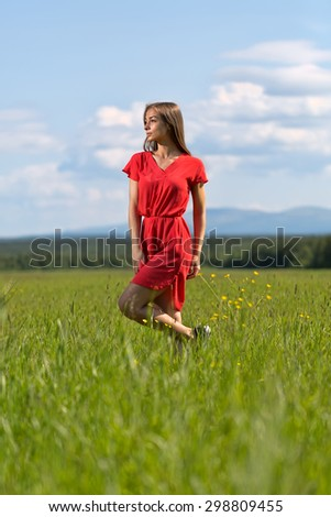 Young girl in a red dress on lawn with blue sky with clouds - stock photo
