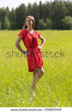 Young girl in a red dress on the lawn and woods - stock photo