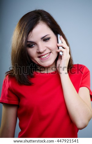 young girl in a red shirt talking on the phone and smiling - stock photo