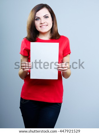 young girl in a red T-shirt and jeans holding a poster, on a gray background - stock photo