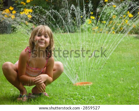 Young girl in a sprinkler