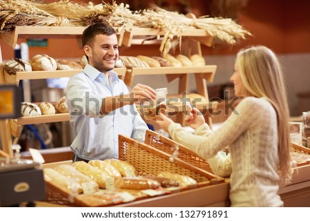 Young girl in a store buying product - stock photo