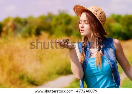 Young girl in a straw hat on the river in the autumn with a frog in his hands