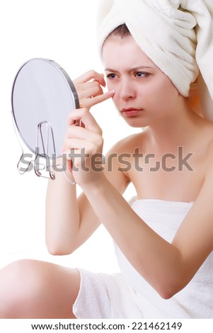 young girl in a towel on his head, sees his face in the mirror. On a white background. Isolated.