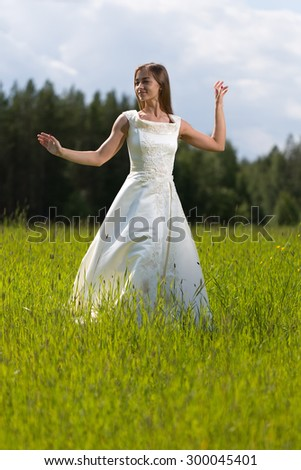 young girl in a wedding dress dancing in the field. - stock photo