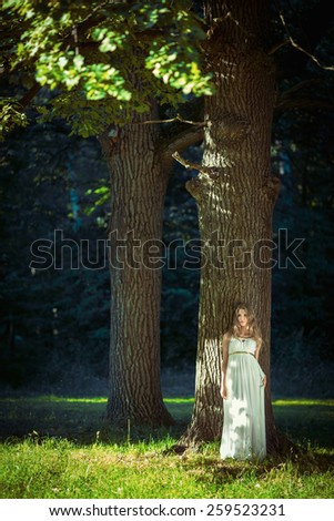 Young girl in a white dress at the tree - stock photo