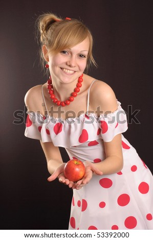 Young girl in a white dress in polka dots, holding an apple - stock photo